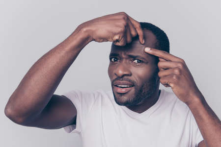 Photo pour Pampering clean and clear concept. Close up photo of upset unsatisfied guy wearing white t-shirt is squeezing out a pimple on the forehead, isolated on grey background - image libre de droit