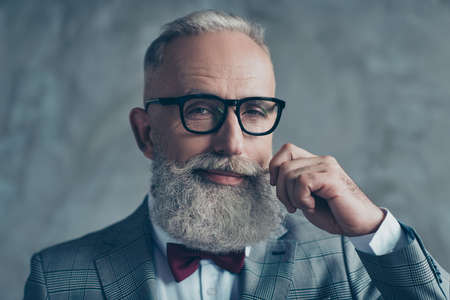 Photo pour Close up portrait of grinning old-fashioned trendy elegant wealthy professional flirty trendsetter hipster grandpa sharp dressed with maroon bow-tie twisting white mustache isolated on grey background - image libre de droit