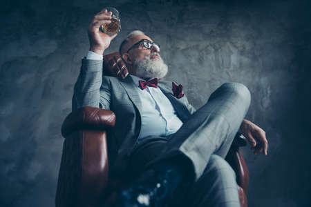 Photo pour Bottom view of attractive, old investor in spectacles, hold glass with brandy, in tuxedo with red bow tie and pocket square, sit in leather chair over gray background, looking at the side - image libre de droit