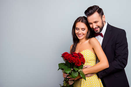 Foto de Portrait photo with copy space of charming, lovely, cute couple in formal wear, dress hugging and looking at  bouquet of red roses, wife and husband celebrating  14 february on grey background - Imagen libre de derechos