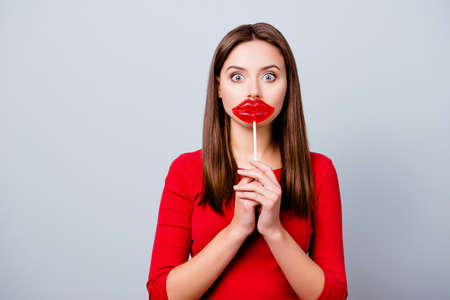 Photo pour Charming, pretty, surprised brunette lady is wishing to have lips like a lollipop, holding bon-bon on stick near mouth, with wide open eyes, standing over gray background - image libre de droit