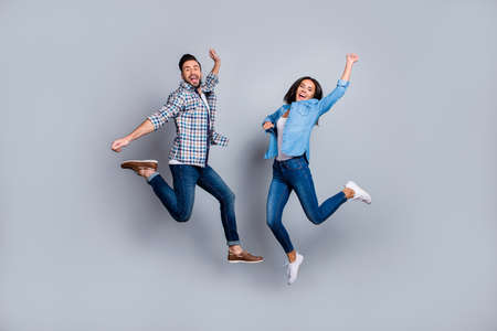 Foto de He vs She full length portrait of attractive, playful, cheerful, comic couple in casual outfit, jeans, shirts jumping  over grey background - Imagen libre de derechos
