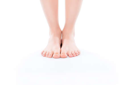 Foto de Cosmetics illness medicine vitality wellness size concept. Cropped close up photo of ideal perfect beautiful attractive woman's bare foot standing on white floor isolated on background copy-space - Imagen libre de derechos