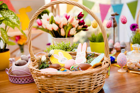 Photo for Close up portrait of wooden basket with easter composition, sweets, choco, gingerbread standing on table over decorative background - Royalty Free Image