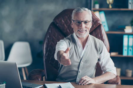 Photo for You are welcome sit down please! Portrait of cheerful experienced qualified successful cheerful excited glad manager expert giving a hand sitting in luxurious modern chair at workstation - Royalty Free Image