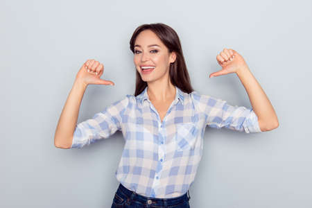Foto de It is me! Portrait of smiling cheerful nice young woman in checkered shirt pointing thumb fingers at her body isolated on grey background, proud of herself, having ego - Imagen libre de derechos
