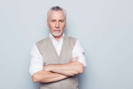 Foto de People individual lifestyle concept. Portrait of virile serious minded self-assured pensive granddad with crossed hands beige knitted waistcoat isolated on gray background copy-space - Imagen libre de derechos