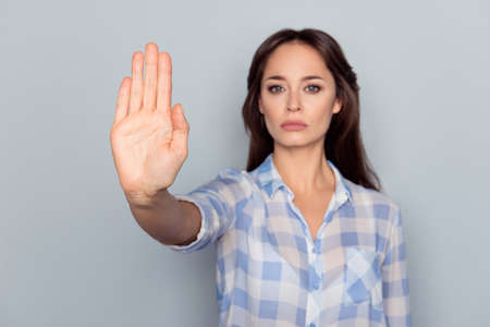Photo for Prohibition symbol. Closeup portrait of young, serious, pretty, charming girl in checkered shirt making stop gesture with palm of her hand on grey background - Royalty Free Image