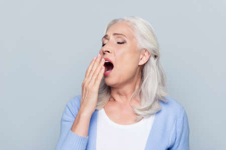 Photo pour Portrait of tired, bored, attractive, aged, lazy woman in  closing her open mouth with palm, she wants to sleep, yawning over grey background - image libre de droit