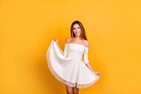 Photo for Sensual, romantic girl with naked shoulders holding for the bottom of the skirt, showing her dress, looking at camera standing over yellow background - Royalty Free Image