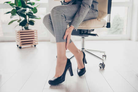 Photo pour Concept of getting varicose because of wearing high heels. Cropped close up photo of woman's legs wearing grey trousers and black modern shoes, hand is touching a leg - image libre de droit