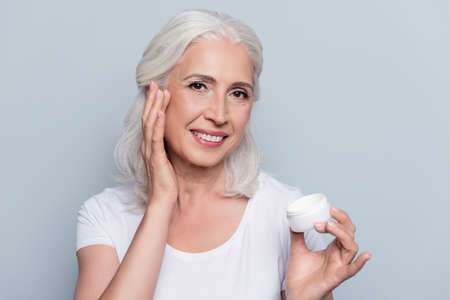 Photo pour Perfect, pretty, woman using day, night cream, holding jar of cosmetic product looking at camera over gray background - image libre de droit