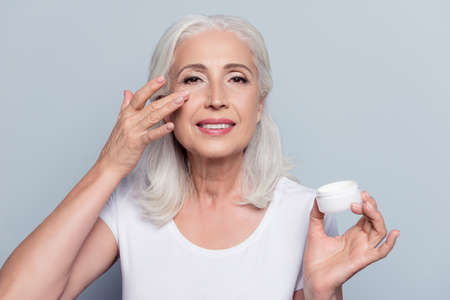 Photo pour Perfect, pretty, woman applying eye cream, holding jar of cosmetic product looking at camera over gray background - image libre de droit