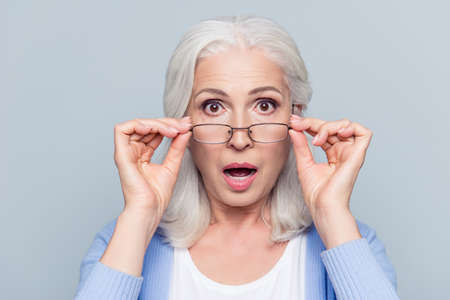 Photo for Close up portrait of stylish, aged, charming, surprised, shocked woman holding eyelets peek out glasses with wide open eyes and mouth over grey background - Royalty Free Image