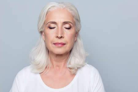 Foto de Close up portrait of confident concentrated mature woman with wrinkles on face, with closed eyes, with nude make up, isolated on gray background - Imagen libre de derechos