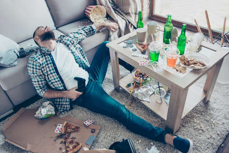 Foto de Drunk sick tired exhausted wearing checkered shirt and denim jeans bearded guy is sitting on the floor holding a joystick he is surrounded by mess and leftovers after global home party and celebration - Imagen libre de derechos