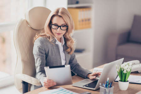 Photo for Pretty, charming, blonde woman using, browsing, typing, searching, expertising, working online on computer and tablet in workplace, using wi-fi internet - Royalty Free Image