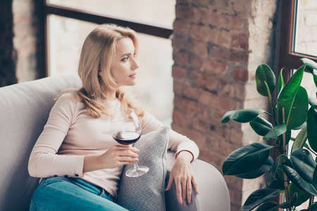 Photo pour Charming, attractive, pretty, stylish woman, having glass with wine in hand sitting on couch with serious expression looking at window, thinking about something - image libre de droit