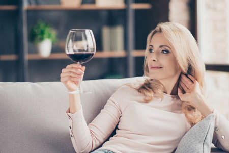 Foto de Portrait of pretty, charming, attractive, stylish connoisseur woman sitting on couch having raised glass with red wine in hand, examine, taste beverage - Imagen libre de derechos