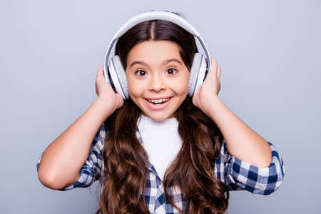 Foto de Close up portrait of happy joyful, cute, shocked kid holding earphones on her head with wide open eyes and mouth listening music standing over grey background - Imagen libre de derechos