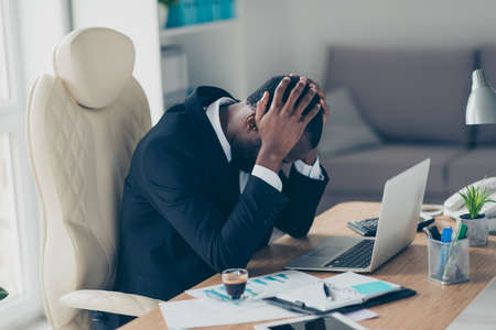 Photo pour Very tired man with black skin economist, holding hands on his hands while sitting at desk tired upset because of hard day - image libre de droit