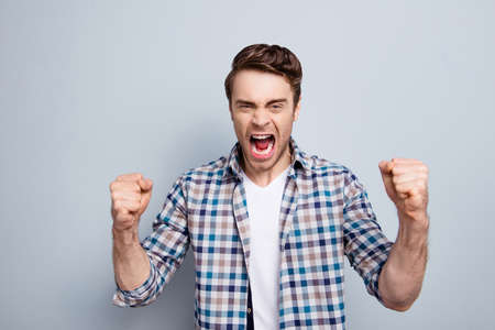Photo pour Aggressive man in checkered shirt with raised fists and open mouth is out of himself, yelling, screaming, shouting with cruelty over grey background - image libre de droit