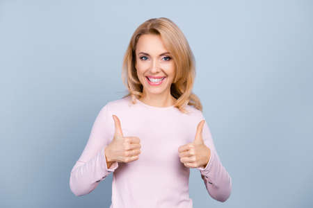 Photo pour Portrait of pretty, charming, glad, nice woman with beaming smile showing two thumbs up sign with hands, isolated on grey background - image libre de droit