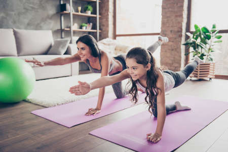 Photo pour Cute sweet cheerful joyful with long hair schoolgirl and slim sportive mom are doing stretching exercises in room om purple mats - image libre de droit