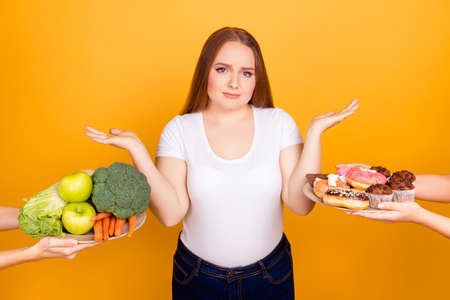 Photo pour Pensive uncertain unsure fatty woman is throwing her hands up because she can't make a choice between healthy products and junk food - image libre de droit