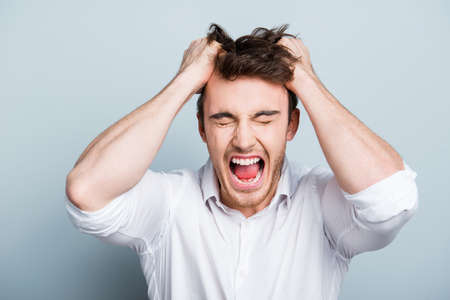 Photo for Emotions, stress, madness and people concept - crazy shouting man rending his hair in white shirt, screaming with close eyes and wide open mouth, holding hands on head over gray background - Royalty Free Image