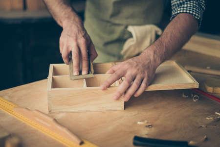 Foto de Close up cropped photo of handicraftsman's hands sanding the surface of handmade wooden box with abrasive paper - Imagen libre de derechos