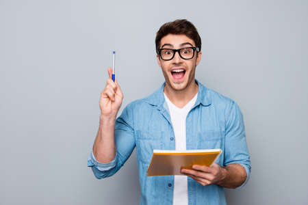 Foto de Handsome, attractive, glad, positive, funny guy in glasses with wide open mouth finally found a solution how to make exercise, having raised pen and notebook in hands - Imagen libre de derechos
