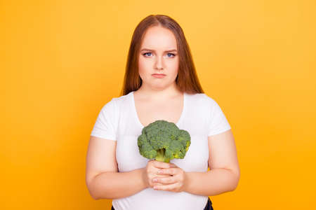 Photo pour Portrait of unhappy upset sad frustrated woman dressed in white tshirt, she is holding green fresh raw broccoli, isolated on bright yellow background - image libre de droit