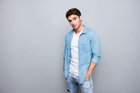 Photo pour Manly, masculine man in jeans outfit, holding hands in pockets of pants, looking at camera, standing over gray background - image libre de droit