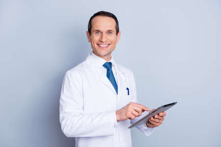 Foto de Portrait of cheerful glad gifted smart with toothy smile doctor using modern pad at work isolated on gray background copy-space - Imagen libre de derechos
