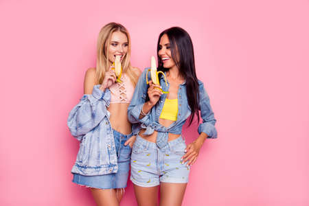 Foto de Beautiful attractive lovely careless charming flirty coquettish women clothed in denim stylish shirts, tops, shorts and skirt are fooling around and eating bananas, isolated on bright pink background - Imagen libre de derechos