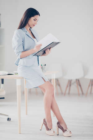 Photo pour Full length, side view, half face profile of charming, pretty, nice, cute financier lean on desk, holding clipboard in hands - image libre de droit
