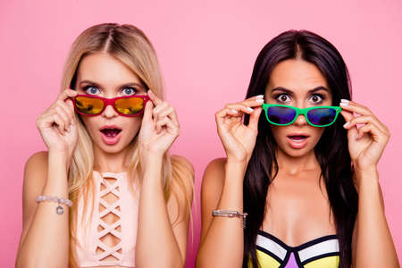 Foto de Pretty, charming, astonished, frustrated impressed, stressed, depressed ladies, tourists looking out glasses with wide open eyes and mouth, holding eyelets with hands, isolated on pink background - Imagen libre de derechos