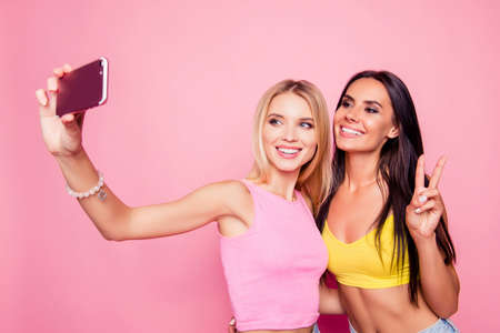 Foto de Two beautiful pretty cheerful smiling attractive charming girlfriends dressed in colorful tops are making a selfie and demonstrating v-sign, isolated on pink background - Imagen libre de derechos