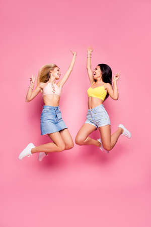 Photo for Attractive, comic, pretty sisters in casual outfit jumping with hands up, pink background - Royalty Free Image