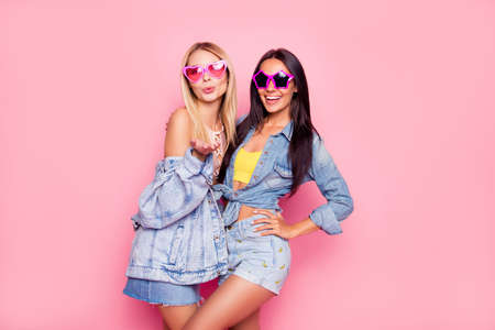 Foto de Beautiful playful cheerful women dressed in fashionable stylish shorts, shirt, jacket, top, funny star and heart glasses are embracing, sending air-kiss, isolated on bright pink background - Imagen libre de derechos