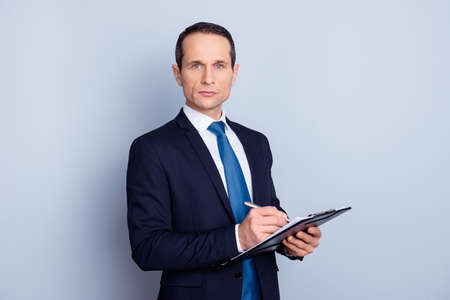 Photo for Portrait of focused clever intelligent concentrated representative with pencil and clipboard writing ideas checking work of staff manager in personnel department isolated on gray background copy-space - Royalty Free Image