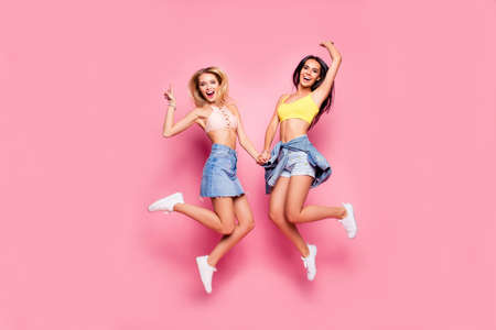 Photo for Beautiful attractive funny joyful cheerful relaxed carefree girls clothed in casual trendy outfit and white shoes are jumping up and holding hands, isolated on bright pink background - Royalty Free Image