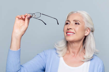 Photo for Old, charming, pretty woman looking through eyeglasses standing over grey background - Royalty Free Image