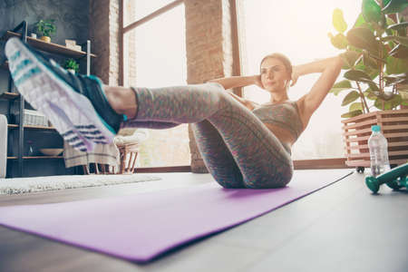 Photo for Low-angle photo of attractive sportive pretty strong muscular flexible woman doing sit-ups and holding legs in air trying to keep balance in reflection, sun glare, beam, ray, sunny day - Royalty Free Image