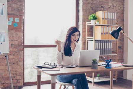 Photo for Attractive cheerful joyful glad trainee looking at monitor and rejoicing at modern workstation - Royalty Free Image