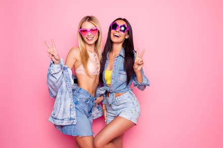Foto de laughing girls in summer heart and star shape glasses, jeans wear gesturing peace symbol to the camera over pink background - Imagen libre de derechos