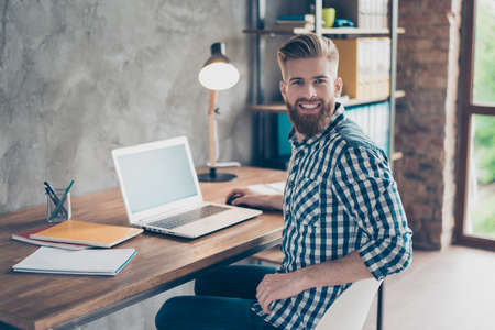 Photo for Cheerful joyful excited clever manager wearing casual modern stylish checkered shirt fixing netbook coding upgrading installing programming using netbook looking at camera sitting at workstation - Royalty Free Image