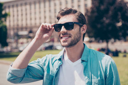 Foto de Portrait of handsome careless cheerful carefree delightful feeling good man wearing casual cozy comfortable outfit clothes touching correcting fixing glasses, sunshine, city, town, lifestyle - Imagen libre de derechos