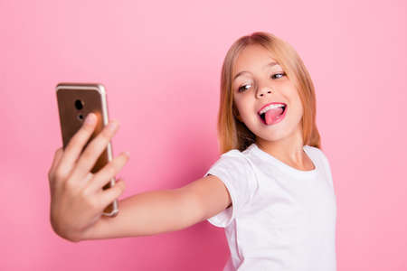 Photo pour Addiction lifestyle leisure style trend play game concept. Close up portrait of cute lovely sweet charming with toothy smile taking selfie girl on mum's phone isolated on pink background - image libre de droit